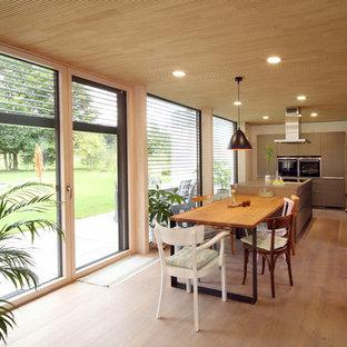 Ispirazione per una grande cucina design con ante lisce, isola, lavello da incasso, ante marroni, elettrodomestici neri, pavimento in legno massello medio, pavimento marrone e top marrone