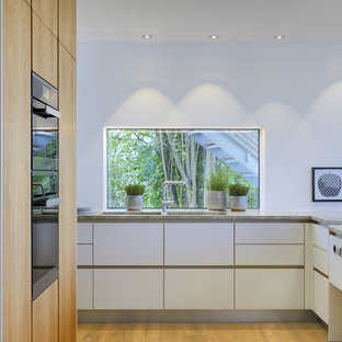 Large contemporary l-shaped open plan kitchen in Other with an integrated sink, flat-panel cabinets, white cabinets, limestone benchtops, black appliances, medium hardwood floors and white splashback.