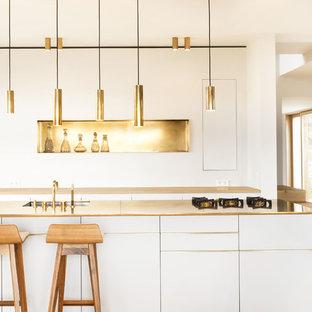 Zweizeilige, Offene, Kleine Moderne Küche mit Unterbauwaschbecken, flächenbündigen Schrankfronten, weißen Schränken, Küchenrückwand in Metallic, hellem Holzboden, Kücheninsel, beigem Boden und gelber Arbeitsplatte in München