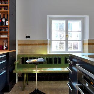 Shabby-Look Küche mit flächenbündigen Schrankfronten, schwarzen Schränken und Edelstahl-Arbeitsplatte in München