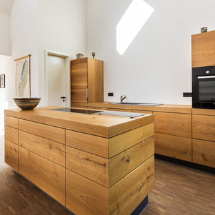 Photo of a medium sized contemporary open plan kitchen in Hamburg with a built-in sink, flat-panel cabinets, medium wood cabinets, wood worktops, white splashback, integrated appliances, medium hardwood flooring, an island and brown floors.