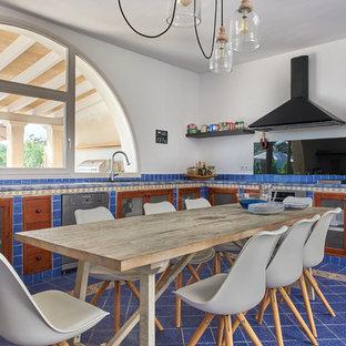 マヨルカ島のビーチスタイルのおしゃれなL型キッチン (ガラス扉のキャビネット、中間色木目調キャビネット、アンダーカウンターシンク、青いキッチンパネル、シルバーの調理設備の、青い床) の写真