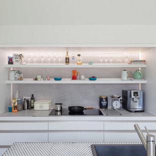 Ejemplo de cocina comedor en L, escandinava, de tamaño medio, con fregadero de un seno, armarios con paneles lisos, puertas de armario blancas, encimera de azulejos, salpicadero blanco, salpicadero con mosaicos de azulejos, electrodomésticos de acero inoxidable, una isla, suelo negro y suelo de terrazo