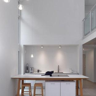 Moderne Küche mit Waschbecken, flächenbündigen Schrankfronten, weißen Schränken, Küchenrückwand in Weiß, Betonboden, Halbinsel, grauem Boden und weißer Arbeitsplatte in Sonstige