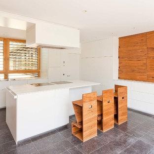 Skandinavische Küche mit Doppelwaschbecken, flächenbündigen Schrankfronten, weißen Schränken, Rückwand-Fenster, Kücheninsel und grauem Boden in Sonstige