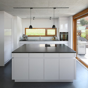 Mid-sized contemporary l-shaped open plan kitchen with a drop-in sink, flat-panel cabinets, white cabinets, black appliances, vinyl floors, with island, black floor, black benchtop and window splashback.