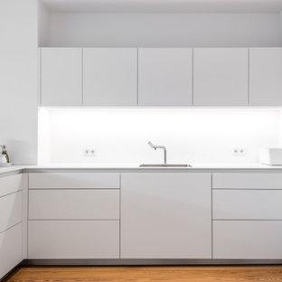 Offene, Mittelgroße Moderne Küche in L-Form mit Waschbecken, flächenbündigen Schrankfronten, weißen Schränken, Mineralwerkstoff-Arbeitsplatte, Küchenrückwand in Weiß, Glasrückwand, weißen Elektrogeräten, hellem Holzboden, Halbinsel und weißer Arbeitsplatte in Hamburg