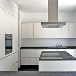 Diseño de cocina en L, minimalista, de tamaño medio, abierta, con fregadero integrado, armarios con paneles lisos, puertas de armario blancas, encimera de granito, salpicadero blanco, salpicadero de piedra caliza, suelo de pizarra, una isla y suelo negro