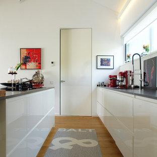 Zweizeilige, Mittelgroße Moderne Küche mit Unterbauwaschbecken, flächenbündigen Schrankfronten, weißen Schränken, braunem Holzboden und Kücheninsel in Sonstige