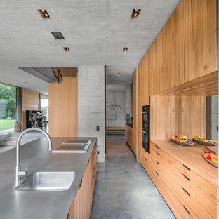 Zweizeilige Industrial Küche mit integriertem Waschbecken, flächenbündigen Schrankfronten, hellbraunen Holzschränken, Rückwand aus Spiegelfliesen, Betonboden, Kücheninsel, grauem Boden und grauer Arbeitsplatte in München