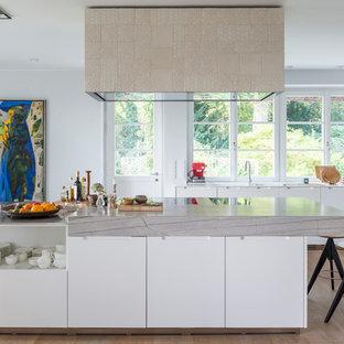 Offene, Zweizeilige, Große Moderne Küche mit flächenbündigen Schrankfronten, weißen Schränken, Küchengeräten aus Edelstahl, hellem Holzboden, Kücheninsel, braunem Boden, Marmor-Arbeitsplatte, Küchenrückwand in Weiß, Rückwand aus Holz und integriertem Waschbecken in Hamburg
