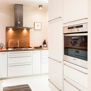 ハンブルクの中サイズのエクレクティックスタイルのおしゃれなLDK (ダブルシンク、フラットパネル扉のキャビネット、白いキャビネット、シルバーの調理設備の、コンクリートの床、アイランドなし、木材カウンター、茶色いキッチンパネル、ボーダータイルのキッチンパネル) の写真