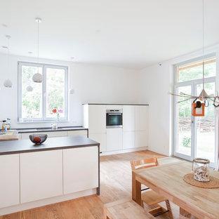 Foto di una cucina scandinava di medie dimensioni con parquet chiaro, lavello a vasca singola, ante lisce, ante bianche, paraspruzzi bianco, elettrodomestici in acciaio inossidabile e penisola