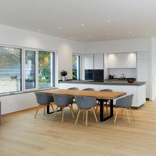 Geräumige, Offene, Zweizeilige Moderne Küche mit flächenbündigen Schrankfronten, weißen Schränken, Küchenrückwand in Weiß, schwarzen Elektrogeräten, hellem Holzboden, Kücheninsel, beigem Boden und grauer Arbeitsplatte in Sonstige