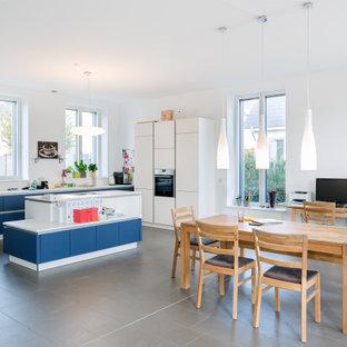 Offene, Große Moderne Küche in L-Form mit Waschbecken, Kassettenfronten, blauen Schränken, Porzellan-Bodenfliesen, Kücheninsel, grauem Boden und weißer Arbeitsplatte in Berlin