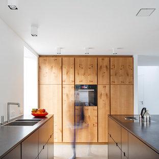 Modelo de cocina de galera, contemporánea, abierta, con fregadero encastrado, armarios con paneles lisos, puertas de armario de madera en tonos medios, encimera de cuarcita, salpicadero blanco, salpicadero de madera, suelo de terrazo, una isla y suelo gris