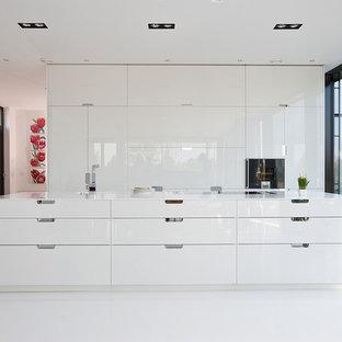 Modelo de cocina contemporánea, grande, abierta, con fregadero de un seno, armarios con paneles lisos, puertas de armario blancas, electrodomésticos con paneles, una isla, salpicadero blanco y suelo de linóleo