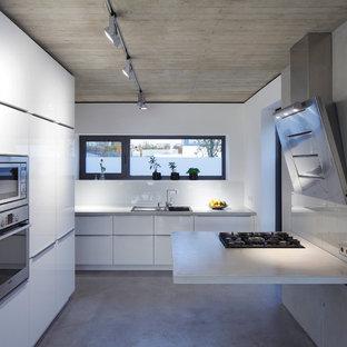 Geschlossene, Große Moderne Küche mit Einbauwaschbecken, flächenbündigen Schrankfronten, weißen Schränken, Betonboden, Betonarbeitsplatte, Küchenrückwand in Grau, Glasrückwand und Küchengeräten aus Edelstahl in Dortmund