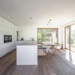 Moderne Wohnküche in U-Form mit Unterbauwaschbecken, flächenbündigen Schrankfronten, weißen Schränken, schwarzen Elektrogeräten, braunem Holzboden, Halbinsel, braunem Boden und grauer Arbeitsplatte in München