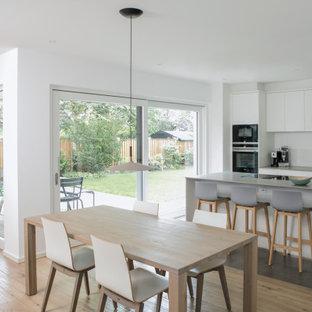 Idéer för mellanstora funkis linjära grått kök och matrum, med en undermonterad diskho, släta luckor, vita skåp, vitt stänkskydd, glaspanel som stänkskydd, svarta vitvaror, ljust trägolv, en köksö, beiget golv och bänkskiva i koppar