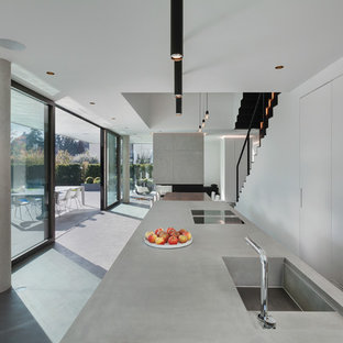 Expansive contemporary galley open plan kitchen in Munich with an integrated sink, flat-panel cabinets, grey cabinets, concrete benchtops, concrete floors, multiple islands and grey floor.