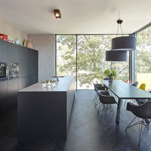 Design ideas for a mid-sized contemporary galley eat-in kitchen in Cologne with flat-panel cabinets, black cabinets, black appliances, dark hardwood floors, multiple islands, black floor and black benchtop.