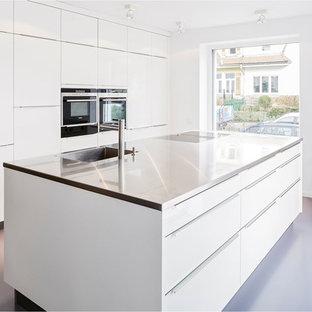 Einzeilige, Große, Offene Moderne Küche mit integriertem Waschbecken, flächenbündigen Schrankfronten, weißen Schränken, schwarzen Elektrogeräten, Kücheninsel und Edelstahl-Arbeitsplatte in Sonstige