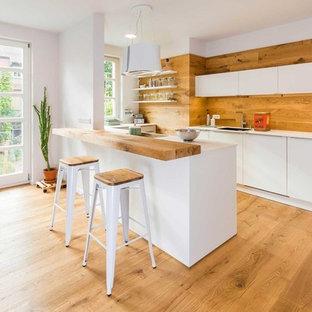 Mittelgroße Nordische Küche mit flächenbündigen Schrankfronten, weißen Schränken, Rückwand aus Holz, braunem Holzboden, Halbinsel, weißer Arbeitsplatte und Unterbauwaschbecken in Nürnberg