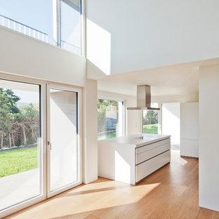 Offene, Große Moderne Küche mit flächenbündigen Schrankfronten, weißen Schränken, Kücheninsel und hellem Holzboden in Stuttgart