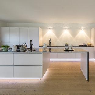 Geräumige, Offene Moderne Küche in U-Form mit flächenbündigen Schrankfronten, weißen Schränken, Granit-Arbeitsplatte, Kücheninsel, hellem Holzboden, braunem Boden, Einbauwaschbecken, Küchenrückwand in Weiß und schwarzen Elektrogeräten in Stuttgart