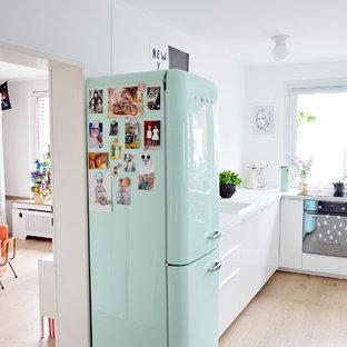 Modelo de cocina comedor en L, nórdica, de tamaño medio, con armarios con paneles lisos, puertas de armario blancas, suelo de madera clara, fregadero encastrado y electrodomésticos de colores
