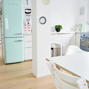 Idéer för mellanstora skandinaviska kök, med vita skåp, vitt stänkskydd, ljust trägolv, släta luckor och färgglada vitvaror
