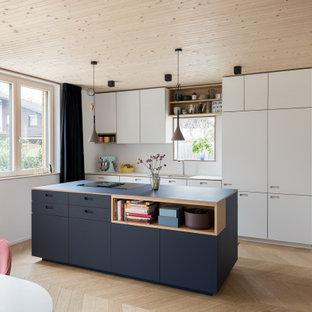 Zweizeilige Moderne Wohnküche mit Unterbauwaschbecken, flächenbündigen Schrankfronten, weißen Schränken, Küchenrückwand in Weiß, Elektrogeräten mit Frontblende, braunem Holzboden, Kücheninsel, braunem Boden und weißer Arbeitsplatte in München