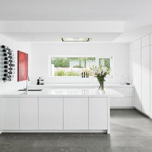 Große Moderne Küche in U-Form mit Unterbauwaschbecken, flächenbündigen Schrankfronten, weißen Schränken, Elektrogeräten mit Frontblende, Halbinsel, grauem Boden und weißer Arbeitsplatte in Stuttgart