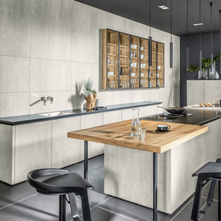 This is an example of a large contemporary galley eat-in kitchen in Other with a drop-in sink, ceramic splashback, black appliances, concrete floors, multiple islands, black floor, black benchtop, flat-panel cabinets, grey cabinets and grey splashback.