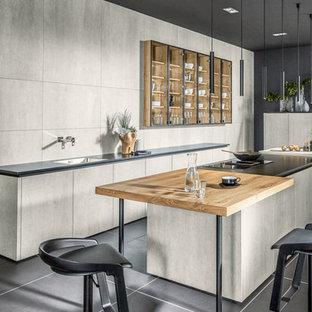 Zweizeilige, Große Moderne Wohnküche mit Einbauwaschbecken, Rückwand aus Keramikfliesen, schwarzen Elektrogeräten, Betonboden, zwei Kücheninseln, schwarzem Boden, schwarzer Arbeitsplatte, flächenbündigen Schrankfronten, grauen Schränken und Küchenrückwand in Grau in Sonstige