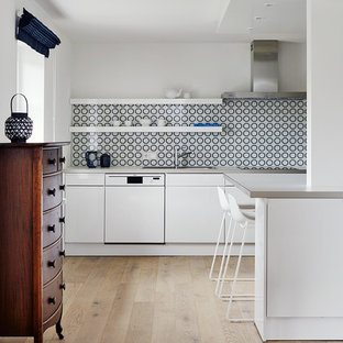 This is an example of a mid-sized eclectic open plan kitchen in Other with a drop-in sink, flat-panel cabinets, white cabinets, blue splashback, porcelain splashback, light hardwood floors, stainless steel appliances, stainless steel benchtops and no island.
