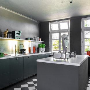 Industrial Küche mit Doppelwaschbecken, flächenbündigen Schrankfronten, grünen Schränken, Marmor-Arbeitsplatte, Küchenrückwand in Metallic, Keramikboden, Kücheninsel, weißer Arbeitsplatte und buntem Boden in Dortmund