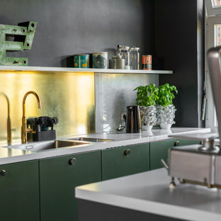 Inspiration for a small industrial galley open plan kitchen in Dortmund with a double-bowl sink, flat-panel cabinets, green cabinets, marble benchtops, metallic splashback, marble splashback, panelled appliances, ceramic floors, with island, black floor and white benchtop.