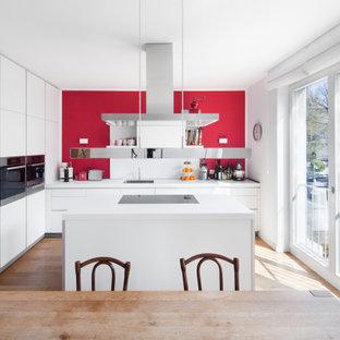 Moderne Wohnküche mit flächenbündigen Schrankfronten, weißen Schränken, Küchengeräten aus Edelstahl, Kücheninsel, Waschbecken, Küchenrückwand in Rot, hellem Holzboden und weißer Arbeitsplatte in Düsseldorf