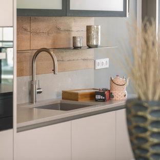 Foto de cocina lineal, contemporánea, de tamaño medio, abierta, con fregadero de un seno, armarios con paneles lisos, puertas de armario beige, encimera de cemento, salpicadero marrón, electrodomésticos negros, una isla y encimeras grises