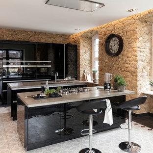 Offene, Einzeilige, Mittelgroße Moderne Küche mit Einbauwaschbecken, flächenbündigen Schrankfronten, schwarzen Schränken, Betonarbeitsplatte, schwarzen Elektrogeräten, zwei Kücheninseln und Zementfliesen in Sonstige