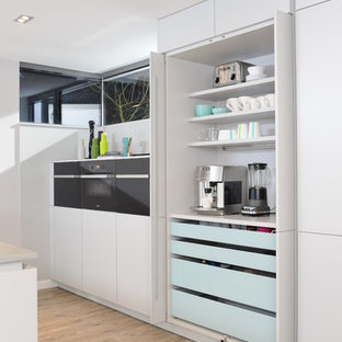 Huge contemporary open concept kitchen designs - Open concept kitchen - huge contemporary galley light wood floor open concept kitchen idea in Berlin with an integrated sink, flat-panel cabinets, white cabinets, concrete countertops, white backsplash, black appliances and an island
