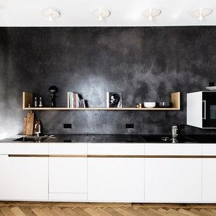Offene, Einzeilige, Kleine Moderne Küche ohne Insel mit integriertem Waschbecken, flächenbündigen Schrankfronten, weißen Schränken, Edelstahl-Arbeitsplatte, Küchenrückwand in Schwarz, Kalk-Rückwand, schwarzen Elektrogeräten, braunem Holzboden und braunem Boden in München
