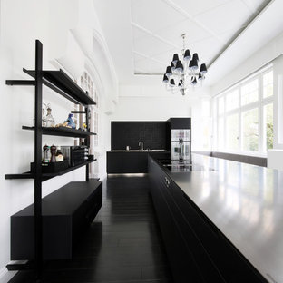 Photo of a large modern single-wall separate kitchen in Hamburg with flat-panel cabinets, black cabinets, black splashback, stainless steel appliances, multiple islands, black floor and black benchtop.