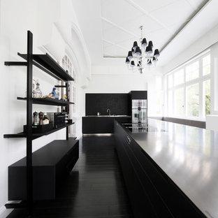 Geschlossene, Einzeilige, Große Moderne Küche mit flächenbündigen Schrankfronten, schwarzen Schränken, Küchenrückwand in Schwarz, Küchengeräten aus Edelstahl, zwei Kücheninseln, schwarzem Boden und schwarzer Arbeitsplatte in Hamburg