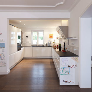 This is an example of a mid-sized contemporary u-shaped open plan kitchen in Essen with an integrated sink, flat-panel cabinets, white cabinets, white splashback, glass sheet splashback, dark hardwood floors and no island.