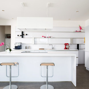 Moderne Küche in L-Form mit flächenbündigen Schrankfronten, weißen Schränken, Küchengeräten aus Edelstahl, Kücheninsel, grauem Boden und weißer Arbeitsplatte in Sonstige