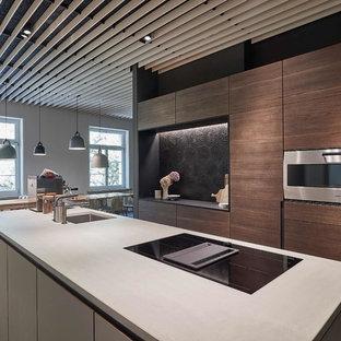 Offene, Zweizeilige, Große Moderne Küche mit Unterbauwaschbecken, flächenbündigen Schrankfronten, dunklen Holzschränken, Betonarbeitsplatte, Küchenrückwand in Schwarz, Rückwand aus Zementfliesen, Küchengeräten aus Edelstahl, Kücheninsel, grauem Boden und grauer Arbeitsplatte in Stuttgart