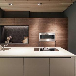 Zweizeilige, Mittelgroße Moderne Wohnküche mit Unterbauwaschbecken, flächenbündigen Schrankfronten, dunklen Holzschränken, Küchenrückwand in Schwarz, Rückwand aus Zementfliesen, Küchengeräten aus Edelstahl, Kücheninsel, grauem Boden und grauer Arbeitsplatte in Stuttgart